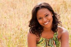 Счастливая женщина сидя в усмехаться поля Стоковое фото RF