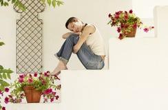 Счастливая женщина сидя на лестнице в саде Стоковая Фотография