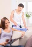 Счастливая женщина сидя на кассете чтения кресла Стоковое Изображение