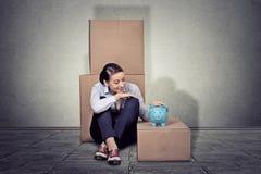 Счастливая женщина сидя на поле при много коробок, двигая вне Стоковые Изображения RF