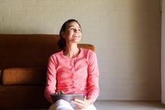 Счастливая женщина сидя на поле с таблеткой сенсорного экрана Стоковое фото RF