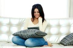 Счастливая женщина сидя на софе и используя планшет Стоковое Фото