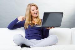 Счастливая женщина сидя на софе и показывая компьтер-книжку, современную технологию Стоковые Фотографии RF