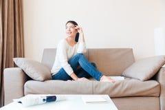 Счастливая женщина сидя на софе Стоковые Фото