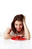 Счастливая женщина сидя на таблице с свежим тортом клубники стоковые фото