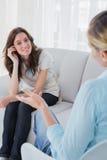 Счастливая женщина сидя при ее терапевт говоря к ей Стоковая Фотография RF