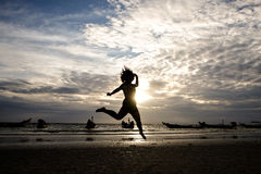 Счастливая женщина скача в заход солнца моря Стоковое фото RF