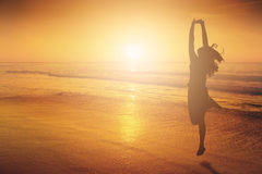 Счастливая женщина скача в силуэт захода солнца пляжа моря стоковое изображение