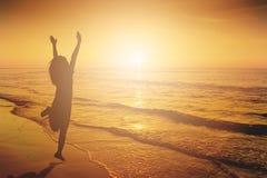 Счастливая женщина скача в силуэт захода солнца пляжа моря стоковое изображение rf