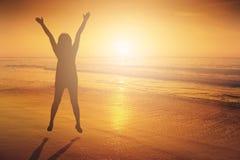 Счастливая женщина скача в силуэт захода солнца пляжа моря стоковое фото rf