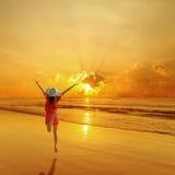 Счастливая женщина скача в силуэт захода солнца пляжа моря стоковые изображения