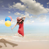 Счастливая женщина скача и держа баллоны на пляже и облаках стоковая фотография