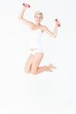 Счастливая женщина скача и держа гантели Стоковые Изображения