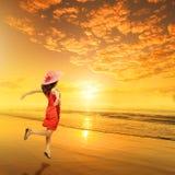 Счастливая женщина скача на заход солнца пляжа стоковые изображения