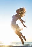 Счастливая женщина скача на море Стоковые Фото