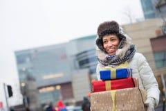Счастливая женщина смотря отсутствующий пока носящ штабелированные подарки во время зимы Стоковое Фото