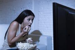 Счастливая женщина смотря телевидение на попкорне еды кресла софы счастливом excited наслаждаясь Стоковая Фотография RF