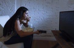 Счастливая женщина смотря телевидение на попкорне еды кресла софы счастливом excited наслаждаясь Стоковые Фото