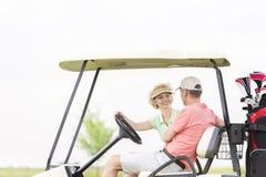 Счастливая женщина смотря человека пока сидящ в тележке гольфа Стоковые Фотографии RF