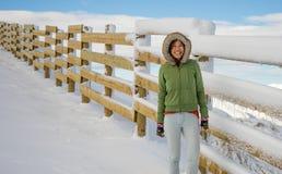 Счастливая женщина стоя на поле лыжи около деревянной загородки Стоковое Изображение