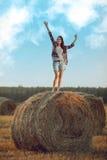 Счастливая женщина стоя на стоге сена Стоковая Фотография