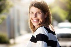 Счастливая женщина стоя outdoors и смеясь над Стоковая Фотография