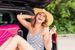 Счастливая женщина с багажом в багажнике автомобиля перемещение карты dublin принципиальной схемы города автомобиля малое Стоковые Фото