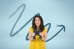 Счастливая женщина с биноклями против голубой предпосылки с стрелкой стоковое фото