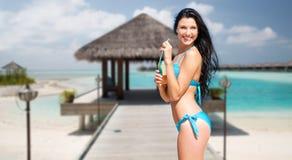 Счастливая женщина с бутылкой питья на пляже лета Стоковая Фотография