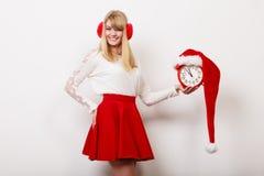 Счастливая женщина с будильником время конца рождества предпосылки красное вверх Стоковое фото RF