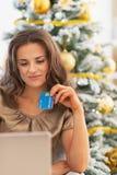 Счастливая женщина с кредитной карточкой и компьтер-книжка около рождественской елки Стоковые Изображения