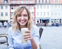 Счастливая женщина с курчавыми светлыми волосами с macchiato latte кофе стоковые изображения rf