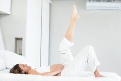 Счастливая женщина с ногой вверх на кровати стоковое фото rf