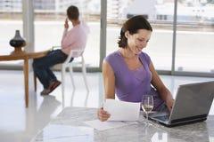 Счастливая женщина с обработкой документов используя компьтер-книжку дома Стоковая Фотография