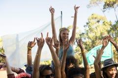 Счастливая женщина с оружиями подняла наслаждаться на музыкальном фестивале стоковая фотография