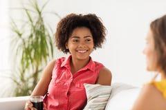 Счастливая женщина с питьем говоря к другу дома Стоковые Изображения