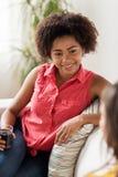 Счастливая женщина с питьем говоря к другу дома Стоковая Фотография
