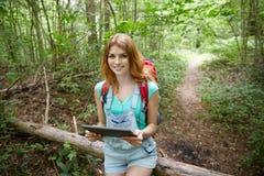 Счастливая женщина с ПК рюкзака и таблетки в древесинах Стоковые Фото