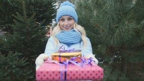 Счастливая женщина с подарками на предпосылке ели видеоматериал