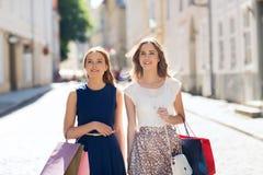 Счастливая женщина с хозяйственными сумками идя в город Стоковые Фото