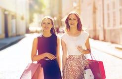 Счастливая женщина с хозяйственными сумками идя в город Стоковое Фото