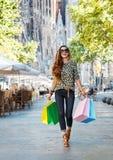 Счастливая женщина с хозяйственными сумками идя около Sagrada Familia Стоковое Изображение RF