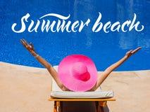 Счастливая женщина с шляпой загорая на lounger солнца бассейном и лето слов приставают к берегу Стоковые Фото