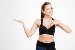 Счастливая женщина фитнеса указывая палец на copyspace на ее ладони стоковое фото