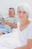 Счастливая женщина читая газету на кровати Стоковые Фото