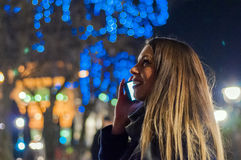 Счастливая женщина чувствуя городской vibe рождества на ноче Счастливая женщина смотря вверх с светом рождества на ноче Стоковые Фото
