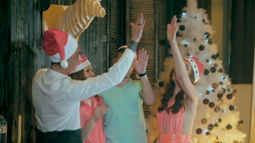 Счастливая, жизнерадостная группа в составе друзья на рождественской вечеринке Приветствие в камеру, имеющ потеху усмехаясь празд сток-видео