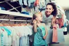 Счастливая жизнерадостная женщина при малый ребенок выбирая одежды Стоковая Фотография RF