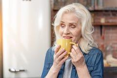 Счастливая зрелая дама ослабляя с горячим напитком стоковая фотография