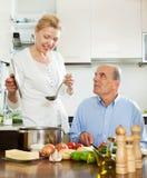 Счастливая зрелая женщина варя с супругом в кухне Стоковое фото RF